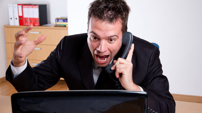 Man-Angry-at-Computer-on-Phone-in-Office